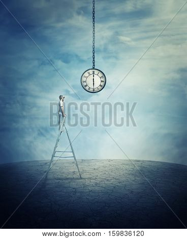 Young boy stay on the top of a ladder in the middle of a cracked desert ground looking at a huge suspended clock.