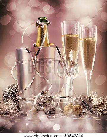 Two glasses of champagne with bottle in cooler on a pink background selective focus
