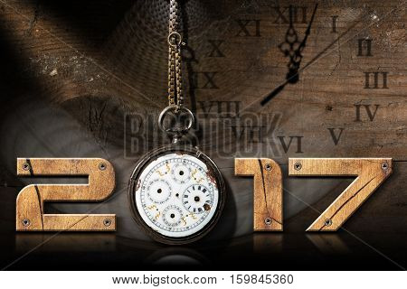 2017 New Year - Wooden numbers with an old and broken pocket watch with chain on a wooden background