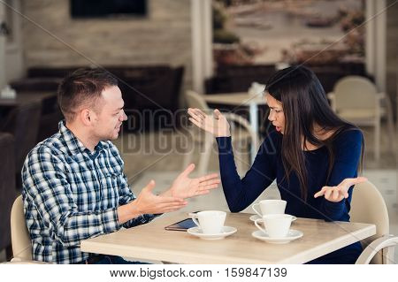 Young couple arguing in a cafe. She's had enough, boyfriend is apologizing. Relationship problems