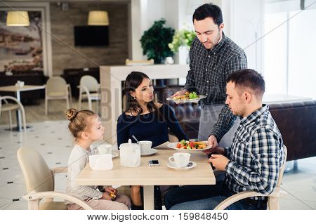 Happy family having breakfast at a restaurant.