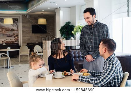 Waiter serving a family in a restaurant and bringing a full plate.