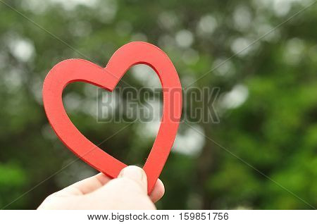 A mans hand holding a red wooden heart up against a green background