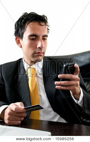 Business man at office paying with his credit card trough his cell phone