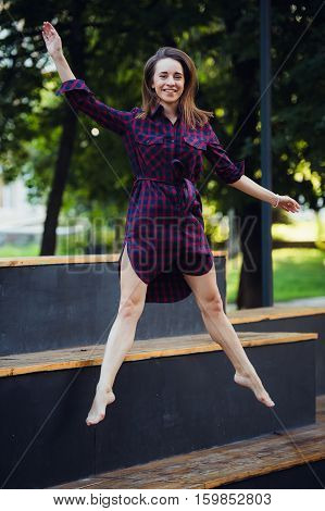 Girl does pirouette walking on a tiptoes against summer park