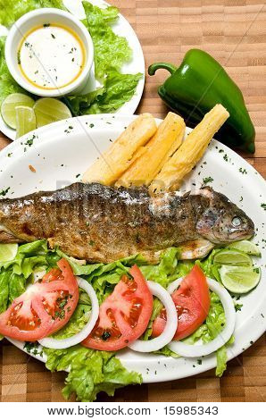Ecuadorian food series: fried fish on a plate with yucca and salad