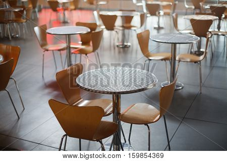 Cafe in airport with brown round tables