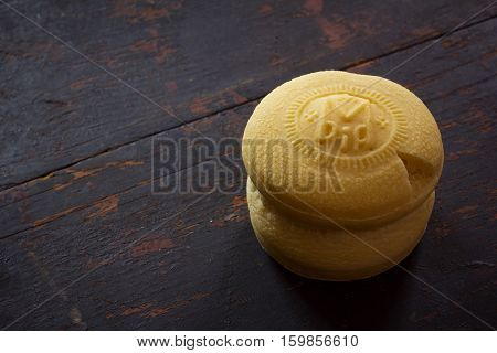 Theotokion service unleavened bread taken out with a particle for Eucharist in the Orthodox Church on the old black wood background with copy space close-up