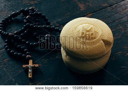Theotokion service unleavened bread taken out with a particle for Eucharist in the Orthodox Church and the rosary with a crucifix close-up. Toned photo
