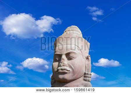 Ancient stone face in Angkor Wat complex on blue sky background Siem Reap Cambodia Southeast Asia. UNESCO World Heritage Site. Scenic landscape. Popular asian landmark famous destination of Cambodia