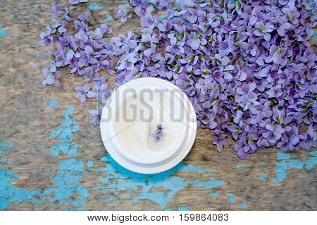 Gathered viola flower (Viola Odorata) with handmade cream. Raw materials for essential oils organic cosmetics. Flowers on grunge wooden background with craquelure. overhead (top) view. Selective focus.