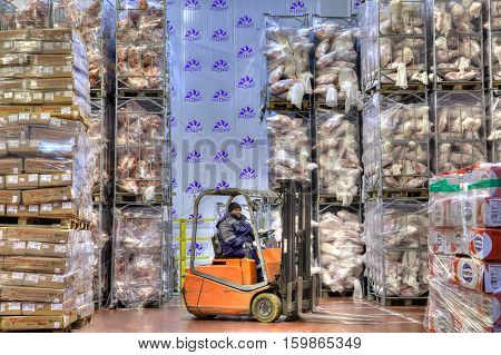 Saint-Petersburg Russia - October 31 2016: Forklift stacker working in very cold stores cold storage refrigerated warehousing frozen food.