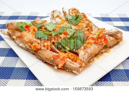 prepared fish with red peppers and some coriander leaves
