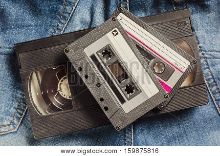 Audio and video Tape Cassettes on the jeans. Vintage toned image