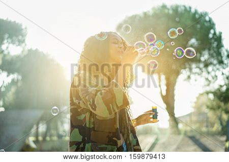 Young afro hair woman blowing soap bubble in city skate park with back sun light - Portrait of african happy girl having fun outdoor - Happiness concept - Focus on mouth - Warm filter with sun flare