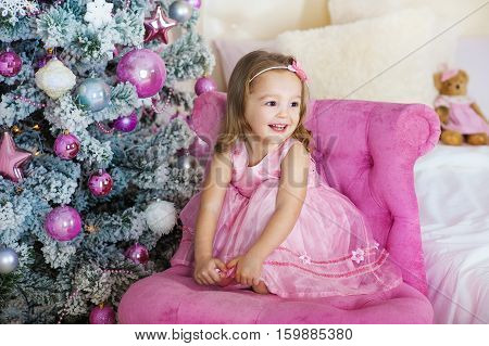 Very nice charming little girl blonde in pink dress sitting on a child's armchair and laughs loudly on the background of Christmas trees in bright interior of the house.