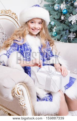 smiling little girl with gift box in a Christmas decorations and christmas thee background. The girl opening Christmas gift. Christmas time. Children's emotions of Santas' presents. Girl look at the camera. Happy New Year
