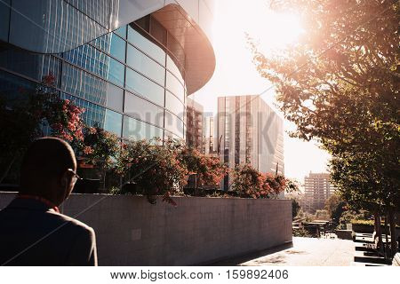 Businessmen near the entry into the business center. Skyscrapers with glass facade. Modern buildings. Concepts of economics, financial, future. Copy space for text. Dynamic composition. Toned