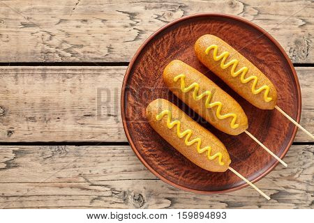 Corn dog traditional American junk food fried hotdog meat sausage snack with mustard snack treat coated in a thick layer of cornmeal batter on stick unhealthy eating on rustic wooden table.