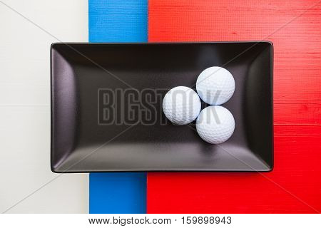 Black ceramic dish with golf balls on over whiteblue and red wooden table rectangle dish