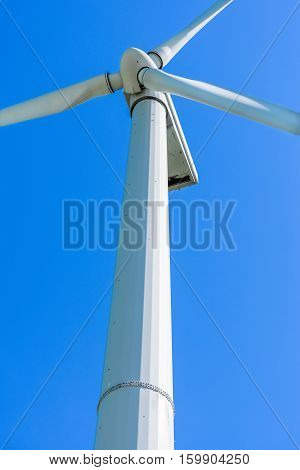 Wind generator, on a background of blue sky. An alternative source of electricity. Sunny day.