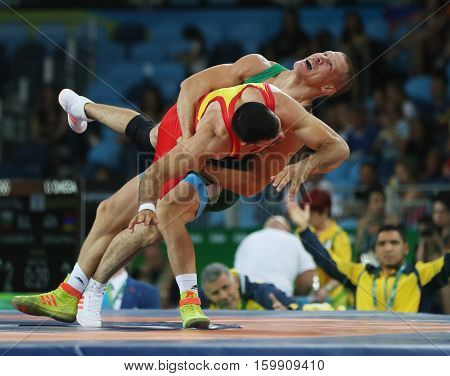 RIO DE JANEIRO, BRAZIL - AUGUST 14, 2016:Wrestler Peter Basci of Hungary (in green) and  Carlos Andres Munoz Jaramillo of Columbia during Men's Greco-Roman 75 kg Qualification of the Rio 2016 Olympics