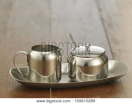 stainless steel milk and sugar container on the wooden background
