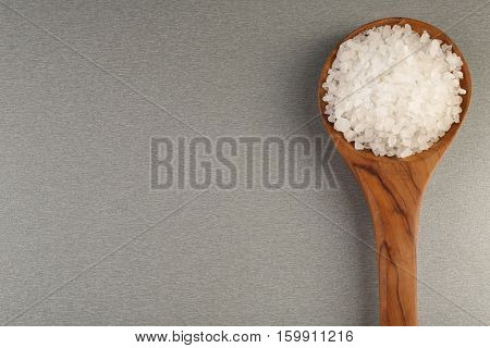 Spoon with sea salt on color background