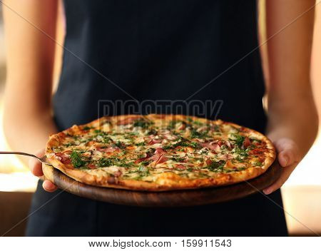 Young woman holding plate with tasty pizza, close up view