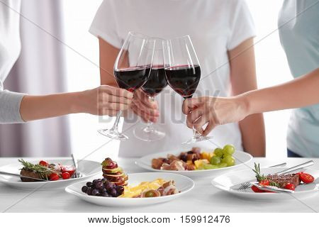 Women clinking glasses with wine and delicious dishes on table in restaurant