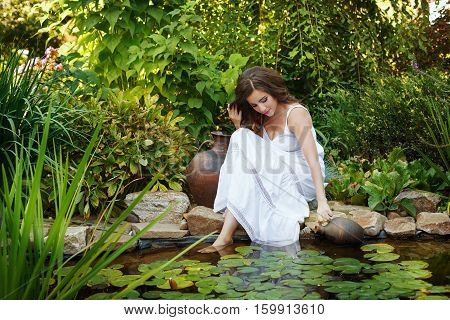 Lovely girl in a white dress draws water from a pond in the little old pitcher. Big old clay jug standing beside her.