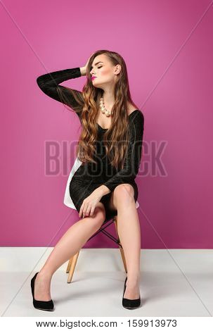 Gorgeous young woman in black evening dress posing on pink background