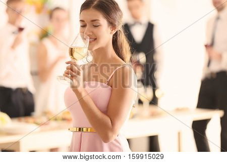 Beautiful young woman drinking champagne at party