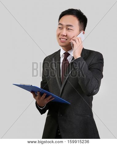 Handsome Asian man holding clipboard while talking by mobile phone, on light background