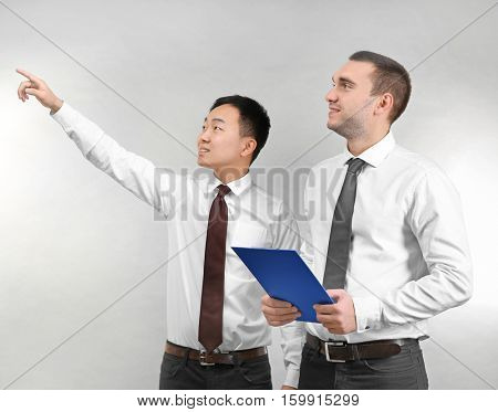 Handsome men discussing something on light background