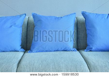 Blue Pillows On Light Blue Sofa With Blue Wall Background