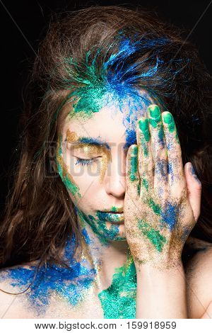 Beautiful face with colored paint on a black background. Beautiful girl. Colorful makeup. Fashionable woman.