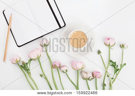 Beautiful spring Ranunculus flowers empty notebook and cup of coffee on white table from above. Greeting card. Breakfast. Pastel color. Clean space for text. Flat lay style.