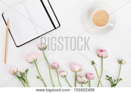 Beautiful spring Ranunculus flowers empty notebook and cup of coffee on white desk from above. Greeting card. Breakfast. Pastel color. Clean space for text. Flat lay style.