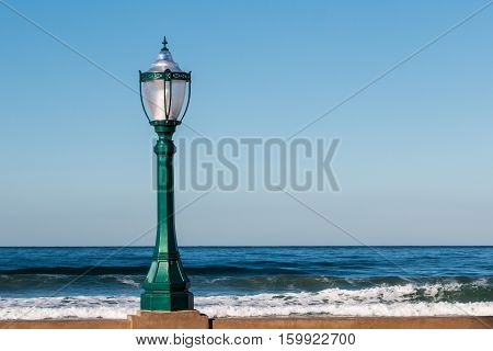 Street lamp on wall with ocean background.