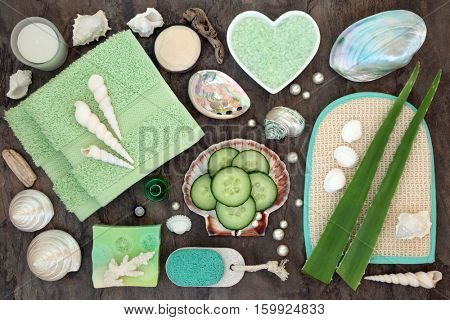 Aloe vera and cucumber spa beauty treatment with bathroom skincare accessories including soap, flannel, body scrub, pumice, moisturising cream with shells and pearls.