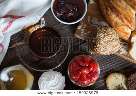 Breakfast table with pastries and black tea, top view