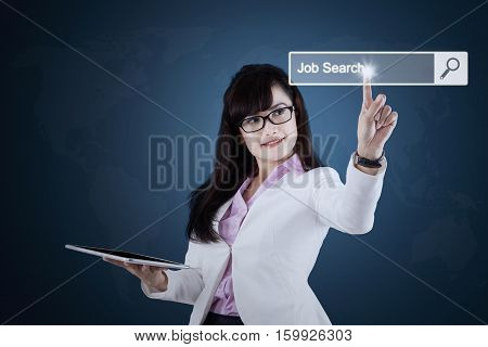 Photo of young businesswoman holding a digital tablet and pressing job search button on the virtual screen