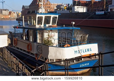 POLAND GDANSK - DECEMBER 14 2014: Small ship with Christmas tree on board. Moored in the historic part of Gdansk on the Motlawa River. Gdansk is a popular center of tourism.