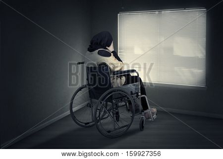 Image of disabled woman sitting in a wheelchair and expressing depressed while looking at the window