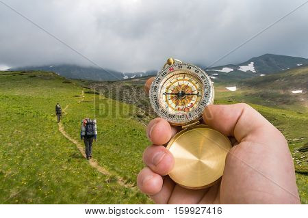 Traveler Man With Compass Seeking A Right Way In The Mountains