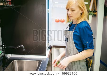 Blonde Woman In A Dress And An Apron In The Kitchen Has Been Cooking