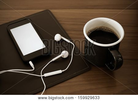 Listening to music on smartphone while drinking coffee vintage style