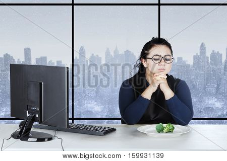 Young woman praying in front of a plate of broccoli while sitting on the chair with winter background on the window