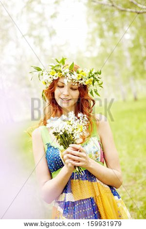 Portrait of a pretty girl walking in wreath and with wildflowers in the wood